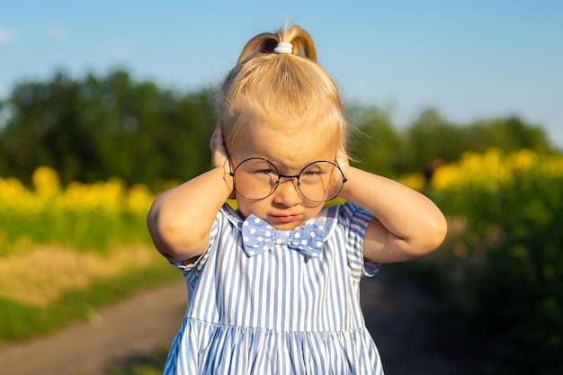Klein meisje in een jurk en bril op de achtergrond van een zonnebloem veld.