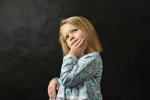 Klein meisje in een jurk permanent en dromen