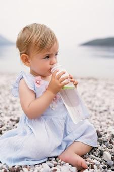 Klein meisje in een jurk zit op een kiezelstrand en drinkt water uit een fles