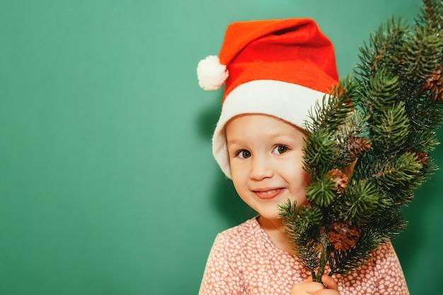 Klein meisje in een kerst pet met een dennenboom glimlacht op een groene muur. vrolijk kerstfeest concept. vakantie aan huis. kopieer ruimte