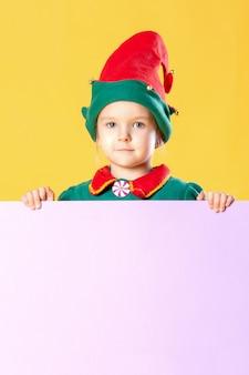 Klein meisje in een kerstelfkostuum. plaats voor tekst op een roze achtergrond, kopieer ruimte.
