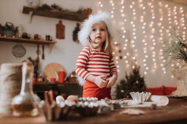 Klein meisje in een kerstmuts en rood gestreepte pyjama kookt een kersttaart in een mooie keuken