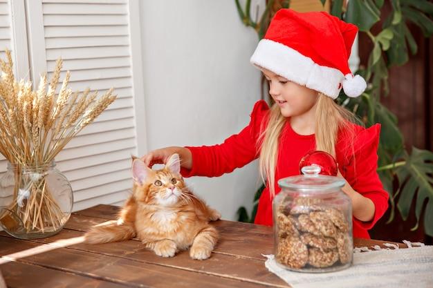 Klein meisje in een kerstmuts met een kat in de keuken