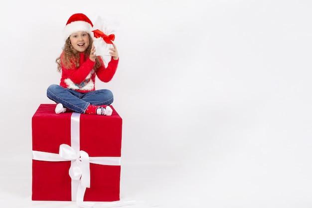 Klein meisje in een kerstmuts zit op een rode kubus met een cadeau in haar handen gelukkige jeugd