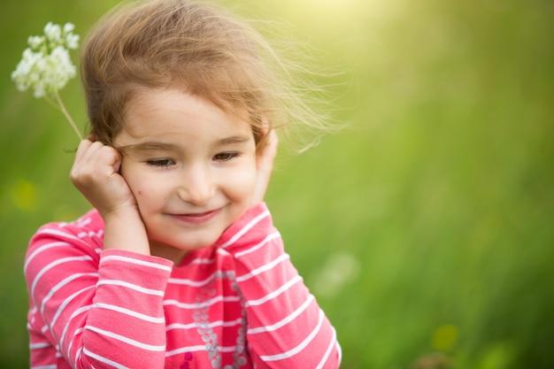 Klein meisje in een koraal gestreept t-shirt op een groene achtergrond in een veld houdt haar gezicht in haar handen en glimlacht sluw. kinderdag, blij kind, milieu- en natuurbescherming, insectenwerend middel