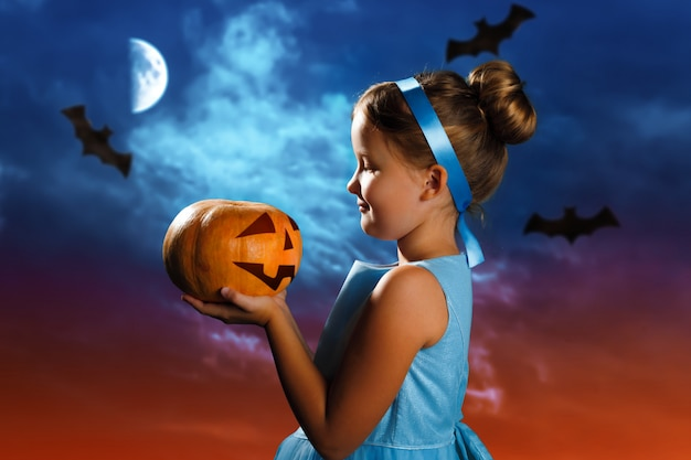 Klein meisje in een kostuum van de assepoester houdt een pompoen op de achtergrond van de avondhemel.