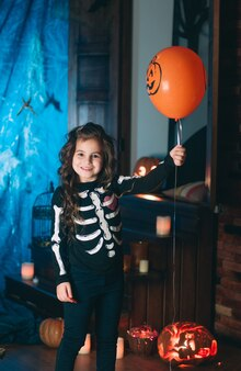 Klein meisje in een kostuum van skelet met oranje ballon