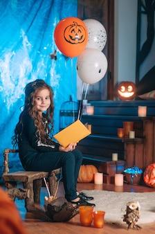 Klein meisje in een kostuum van skelet met oranje en witte ballonnen