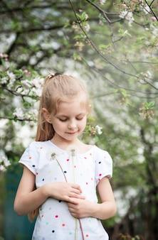Klein meisje in een lentetuin met witte paardebloemen in haar handen