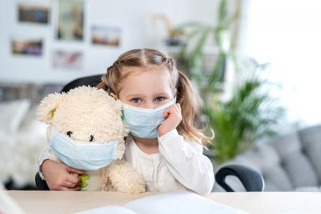 Klein meisje in een masker, knuffelen een teddybeer, op zoek verdrietig, concept van e-learning