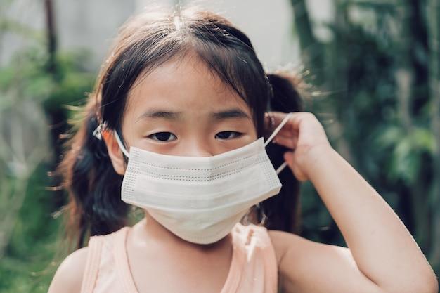 Klein meisje in een medisch masker thuis blijven