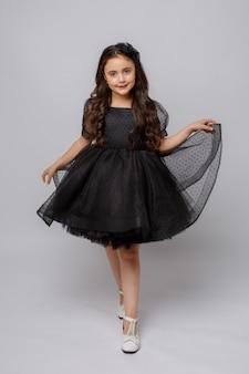 Klein meisje in een mooie jurk op een witte achtergrond