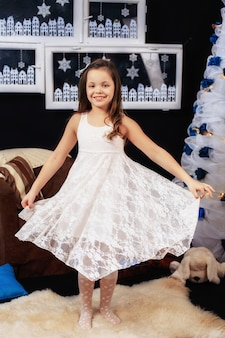 Klein meisje in een mooie witte jurk. het nieuwe jaar en vrolijk kerstfeest
