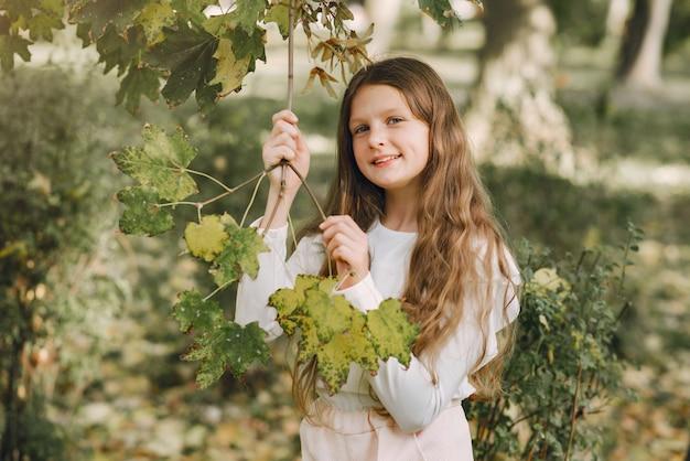 Klein meisje in een park in een witte blouse
