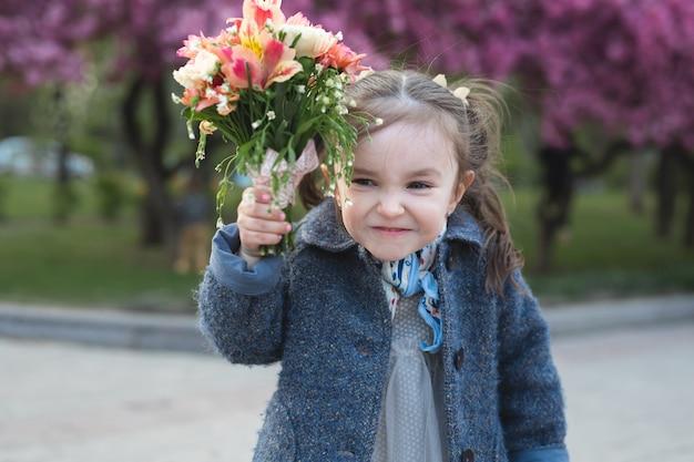 Klein meisje in een park in het voorjaar bedreigt de camera en zwaait met een boeket bloemen.