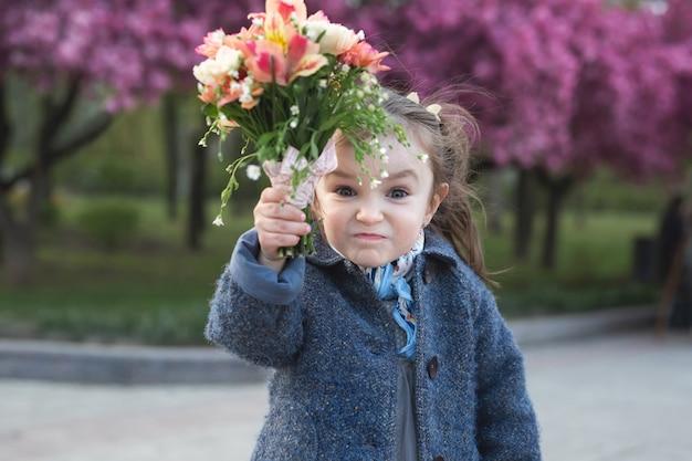 Klein meisje in een park in het voorjaar dreigt een boeket bloemen te zwaaien