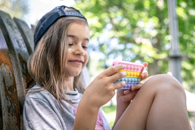 Klein meisje in een pet met een smartphone in een hoesje in de stijl van speelgoed anti-stress pop it.
