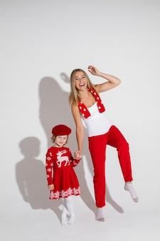 Klein meisje in een rode jurk en hoed poseert voor de camera met haar vrolijke moeder
