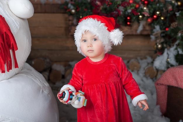 Klein meisje in een rode jurk op een interieur thuis te wachten op de kerstman,