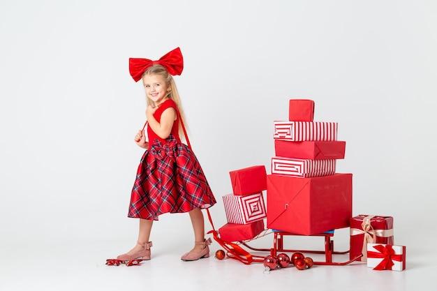 Klein meisje in een rode jurk rolt een slee met cadeautjes voor het nieuwe jaar. witte achtergrond, ruimte voor tekst. het concept van kerstmis
