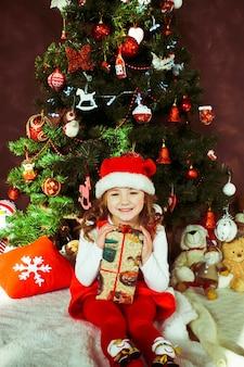 Klein meisje in een rode jurk zit met een huidige vak voor een kerstboom