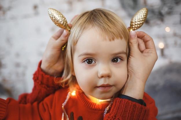 Klein meisje in een rode warme trui. gelukkige jeugd. oren gemaakt van speelgoed