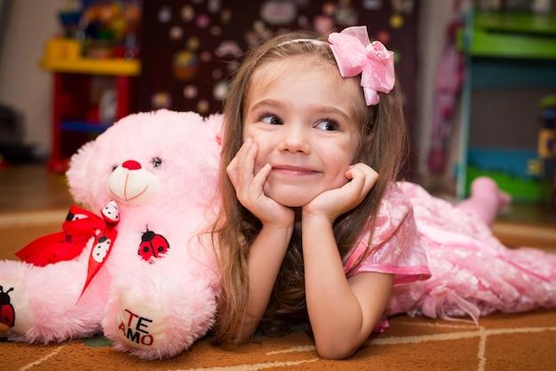 Klein meisje in een roze jurk ligt op de vloer met een speeltje