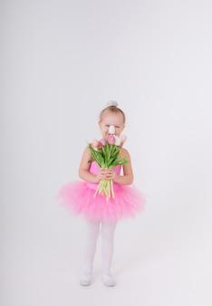 Klein meisje in een roze jurk met een tutu rok staat met een boeket tulpen op een witte muur