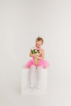 Klein meisje in een roze jurk met een tutu-rok zit met een boeket tulpenbloemen op een witte muur