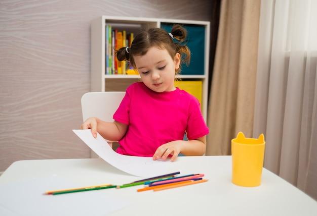Klein meisje in een roze t-shirt zit aan een tafel met papier en kleurpotloden