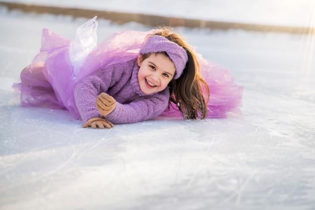 Klein meisje in een roze trui en een pluizige rok op zonnige winterdag rijdt op een open ijsbaan in het park, viel naar beneden en lacht