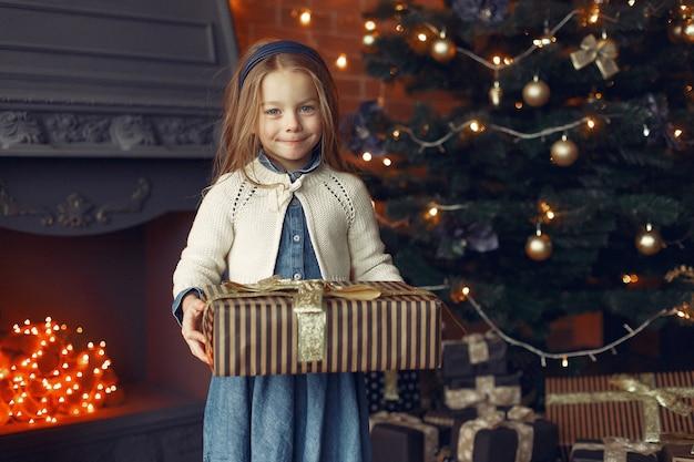 Klein meisje in een schattige jurk in de buurt van kerstboom met heden