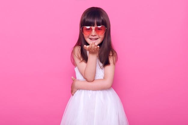 Klein meisje in een slimme witte jurk en een hartvormige bril kijkt naar de voorkant, lacht en stuurt een luchtkus, positieve emoties uiten, geïsoleerd over roze muur