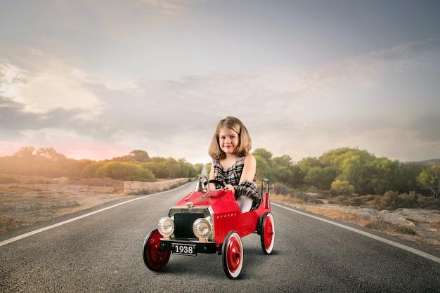 Klein meisje in een speelgoedauto