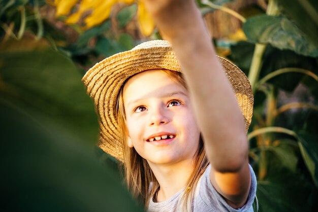 Klein meisje in een strohoed die in het zonnebloemveld speelt kinderen onder zonnebloemen zomer achtergrond