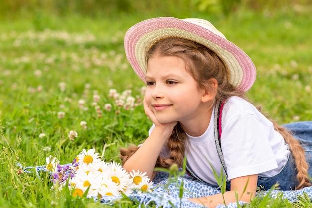 Klein meisje in een strooien hoed rust op het gras.