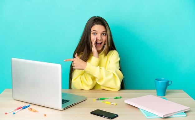 Klein meisje in een tafel met een laptop over een geïsoleerde blauwe achtergrond die naar de zijkant wijst om een product te presenteren en iets te fluisteren