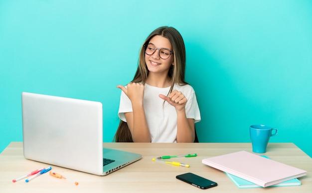 Klein meisje in een tafel met een laptop over een geïsoleerde blauwe achtergrond die naar de zijkant wijst om een product te presenteren