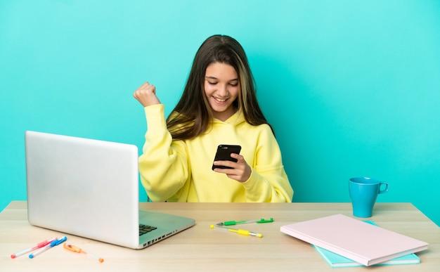 Klein meisje in een tafel met een laptop over geïsoleerde blauwe achtergrond verrast en stuurt een bericht