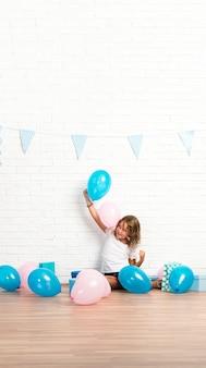 Klein meisje in een verjaardagsfeestje spelen met ballonnen