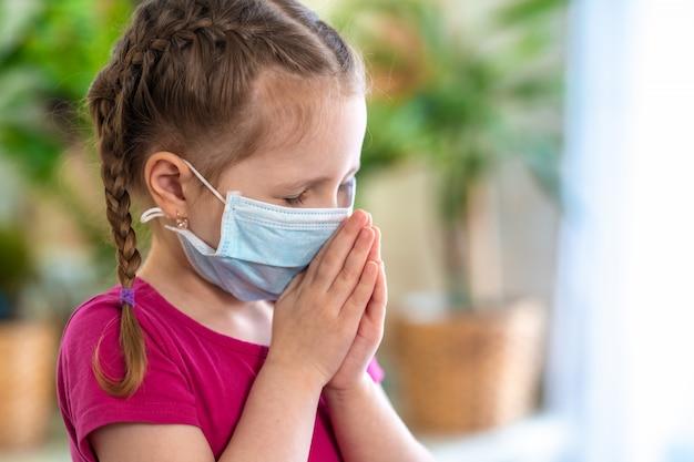 Klein meisje in een virusbeschermingsmasker en covid-19 bidt ze 's ochtends