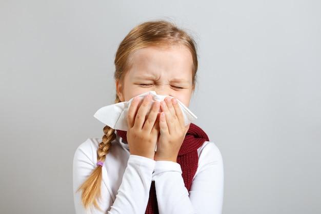 Klein meisje in een warme sjaal blaast haar neus.