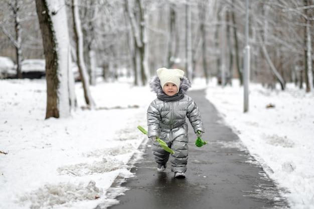 Klein meisje in een warme zilveren jumpsuit rent langs een pad dat helemaal bedekt is met sneeuw.