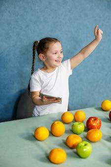Klein meisje in een wit t-shirt houdt een tablet in haar handen en bestudeert de vruchten
