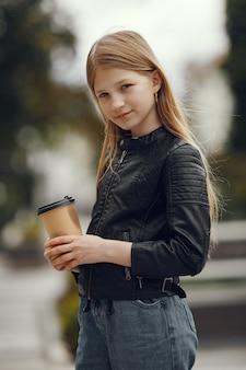 Klein meisje in een wit t-shirt in een zomerstad