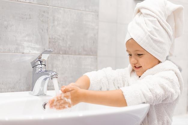 Klein meisje in een witte badjas met een witte handdoek op haar hoofd wast haar handen onder de kraan
