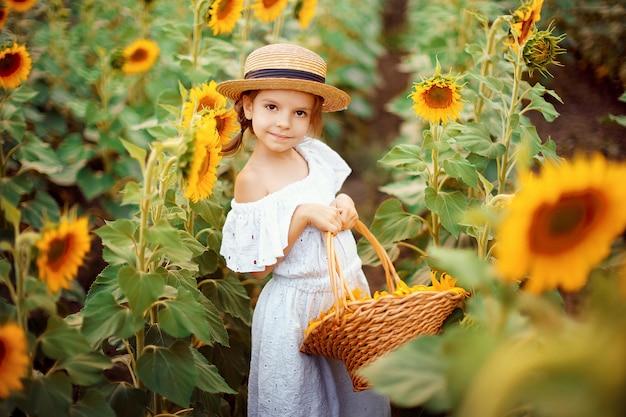 Klein meisje in een witte jurk, een strooien hoed met een mand vol zonnebloemen glimlachen naar de camera in een veld met zonnebloemen