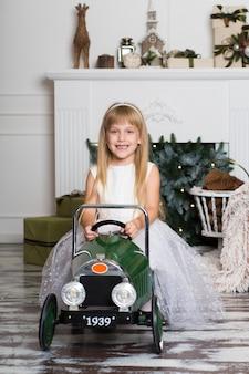 Klein meisje in een witte jurk rijdt op een vintage kinderauto in kerstversiering