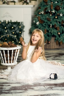 Klein meisje in een witte jurk speelt met dennenappels.