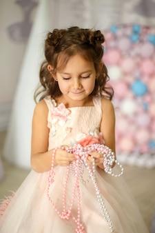 Klein meisje in een witte jurk speelt met kralen